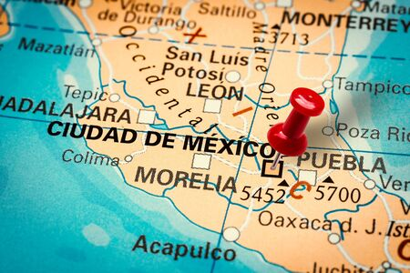 PRAGUE, CZECH REPUBLIC - JANUARY 12, 2019: Red thumbtack in a map. Pushpin pointing at Ciudad de Mexico city in Mexico.