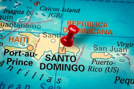 PRAGUE, CZECH REPUBLIC - JANUARY 12, 2019: Red thumbtack in a map. Pushpin pointing at Santo Domingo city in Dominican Republic.