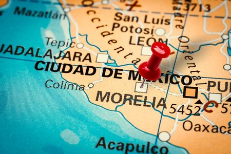PRAGUE, CZECH REPUBLIC - JANUARY 12, 2019: Red thumbtack in a map. Pushpin pointing at Morelia city in Mexico.
