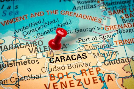 PRAGUE, CZECH REPUBLIC - JANUARY 12, 2019: Red thumbtack in a map. Pushpin pointing at Caracas city in Venezuela.
