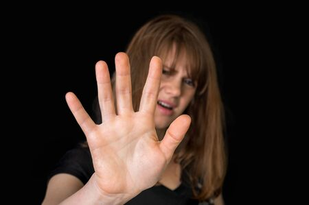 Disgusted woman is showing stop gesture with her hand