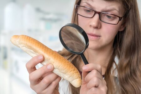 Scientist examines a croissant with magnifying glass - unhealthy dangerous ingredients in foods