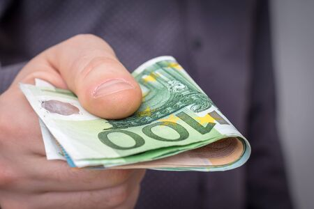 Close-up of european banknotes in hand of man. Businessman giving money for some services - finance concept. Standard-Bild