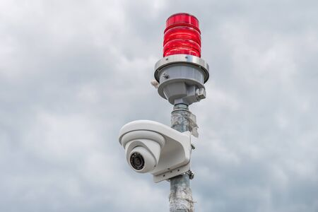 Security camera with red beacon on cloudy sky background 스톡 콘텐츠