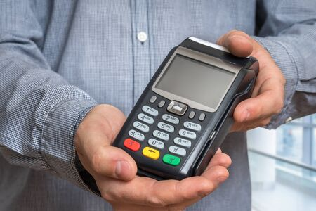 Payment terminal in hand of man - bank money transfer concept Standard-Bild