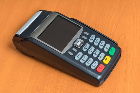 Payment terminal isolated on wooden table background