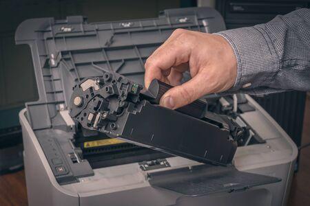 Man is replacing black cartridge in a laser printer