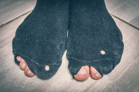 Worn socks with a holes and a fingers sticking out of them - economic crisis concept - retro style