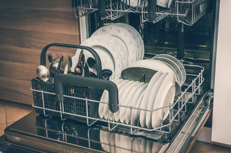 Open dishwasher with clean dishes after cleaning process - retro style