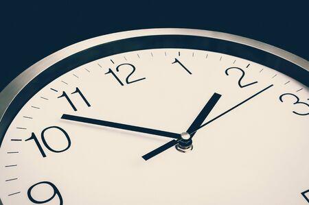 Vue rapprochée de l'horloge isolée sur fond noir - concept de date limite et de temps - style rétro