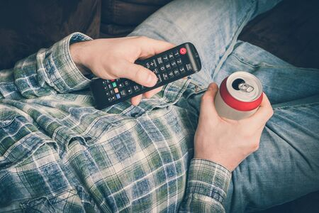Young guy is lying on sofa with TV remote control and drinking beer - retro style