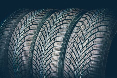 Winter car tires in a row isolated on black background - retro style
