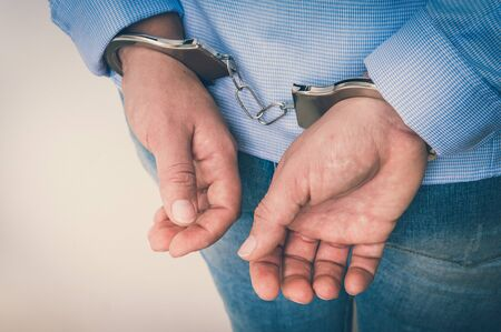Arrested woman in handcuffs with hands behind back - isolated on white background - retro style