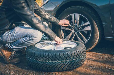 Young man is changing summer car wheel, tire before winter - retro style