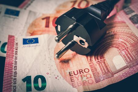 Electric power plug and european money on background - expensive electricity consumption concept - retro style 스톡 콘텐츠