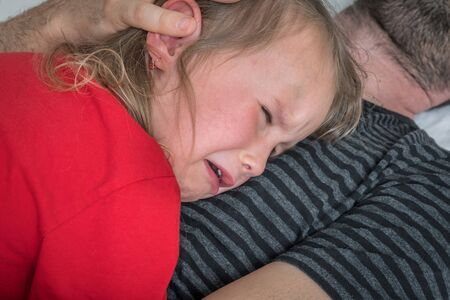 Sad child crying on father's chest - family concept