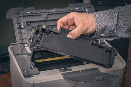 Man is replacing black cartridge in a laser printer