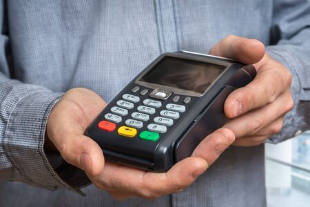 Payment terminal in hand of man - bank money transfer concept 스톡 콘텐츠