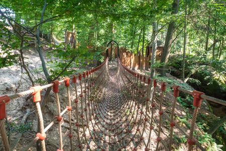 Suspension rope bridge over a rocky valley in forest Stockfoto