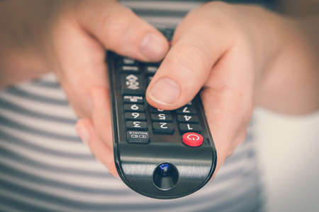 Black remote control in female hands pointing to TV - retro style Stockfoto