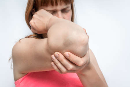 Woman with elbow pain is holding her aching arm - body pain concept