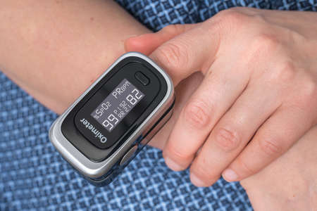 Woman with oximeter is measuring oxygen saturation and heart pulse rate from her finger