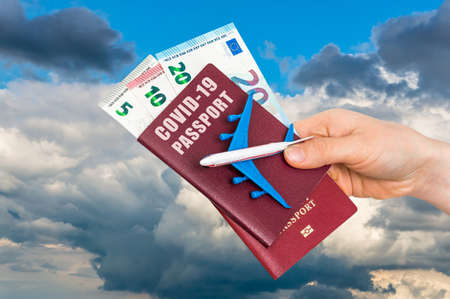 Covid-19 passport for free travel through the world with airplane model in hands of woman