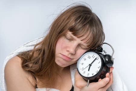Tired woman with alarm clock does not want waking up at early