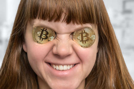 Smiling woman with bitcoin coins in front of her eyes