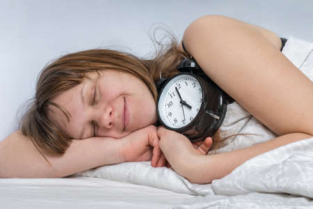 Sleeping woman on pillow with alarm clock before waking up