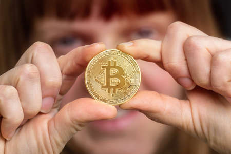 Woman with golden bitcoin in her hand - cryptocurrency concept