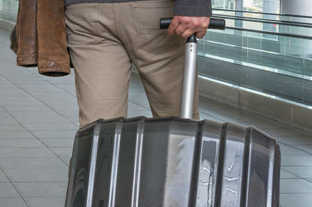 Man with suitcase in hall of airport - travel concept