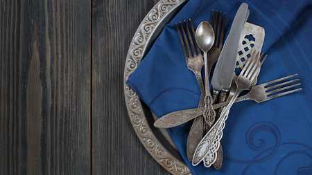 Vintage metal flatware on the old metal tray with pattern on the edge with blue tray cloth on the black wooden texrured background. Top view horizontal 9 x 16 shot. Grey and blue colour. tray is on the right part of the shot. Left is for Copy space.