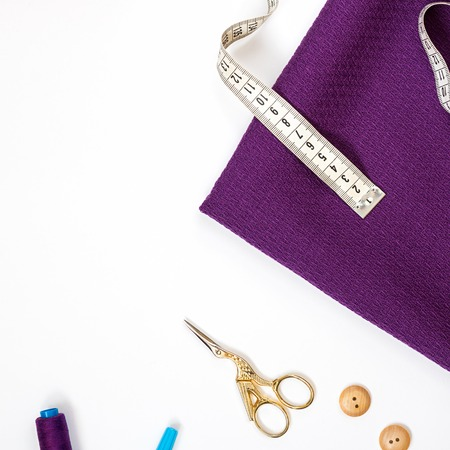 Piece of ultra violet textured square of cloth as diagonal with measuring tape in right upper corner, violet sewing spool and scissors half seen in lower part of square shot. White background. Copy space.