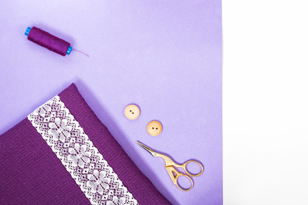 ultra violet textured square of cloth with line of white lace on it as diagonal in left lower corner, violet sewing spool and scissors and two buttons on light violet background and vertical line of white on the right edge. Rightangle horizontal. Copy space.