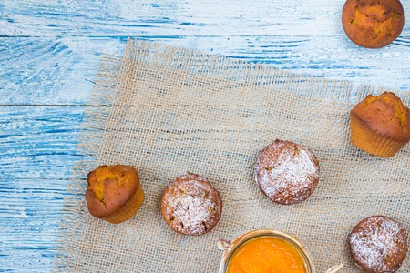 Six orange pumpkin muffins on natural coarse fabric and glass of mashed pumpkin on white blue textured wooden background Top view