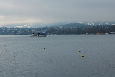 Stemboat on the Lake of Zurich with the background of foggy mountains with snowy tops. Wintertime. Scenery. Blue and grey colours. Sightseeing. Travelling.