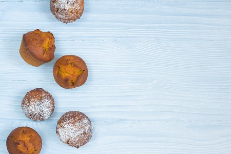 Six bright orange pumpkin muffins, three with sugar powder top on left side of horizontal white and blue textured wooden background Top view. Copy space.