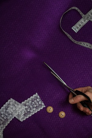 vertical piece of ultraviolet cloth, with measuring tape, buttons, human hands with cutting-out scissors, lace. Cloth is cut diagonally Top view, Copy space,
