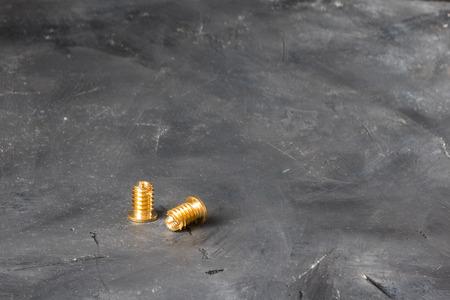 Metall-Gold-Gewindeeinsätze aus Lattin-Metall zum Herstellen sehr harter Verbindungen zwischen Kunststoffdetails, länglicher horizontaler Schuss aus 45-Grad-Winkel auf dem Hintergrund der schwarzen rustikalen Oberfläche