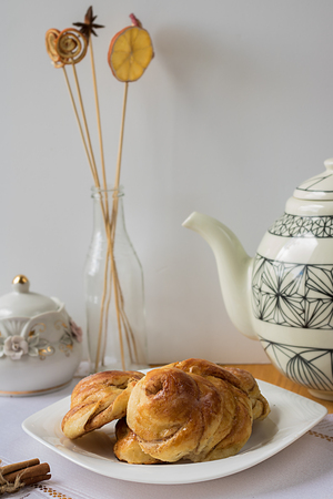 Fresh homemade cinnamon rolls with tea pot and decoration on white background
