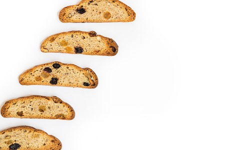 five ong pieces of bright yellow and orange biscotti with white and black sultanas and nuts, dried sweet crispy italian bread On the left part of horizontal shot on the white background with copy space put diagonally Banco de Imagens