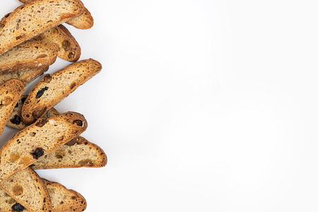 many long pieces of bright yellow and orange biscotti with white and black sultanas and nuts, dried sweet crispy italian bread On the left part of horizontal shot on the white background with copy space