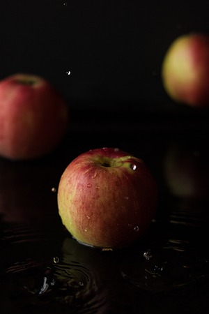 red apple with water drops on black background and defocused apples Banco de Imagens