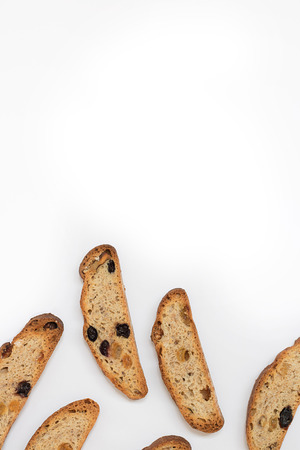 six long pieces of bright yellow and orange biscotti with white and black sultanas and nuts, dried sweet crispy italian bread/ On the lower part of vertical shot on the white background with copy space
