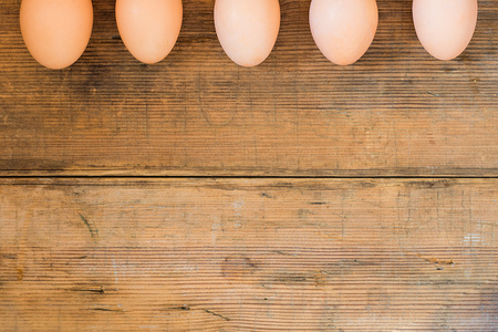 Eggs on wooden brown old textured background. Easter background with copy space for text