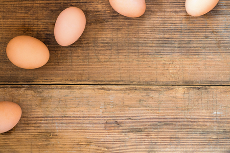 Eggs on edges of wooden brown old textured background. Easter background with copy space for text