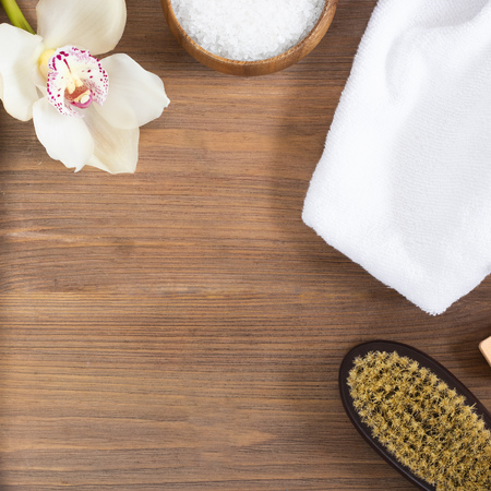woman massage, body and skincare and bath products, sea salt in bowl, white towel, flower, cacus brush for dry massage on brown wooden background. Beauty blogger cosmetics Copy space Mockup Square