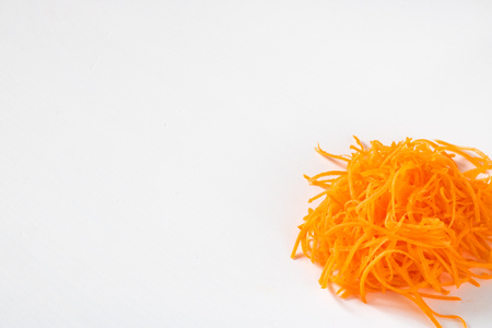 Bright orange fresh grated carrot on the white empty background for copy space, Isolated. Ingrediend. Vegetable. Close up. Healthy. Texture.