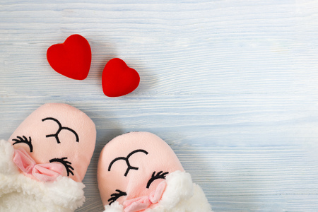 cute sleeping pink lama trendy slippers soft pastel colours with bright red hearts on wooden textured blue background Top view Soft slippers Love Valentine Concept